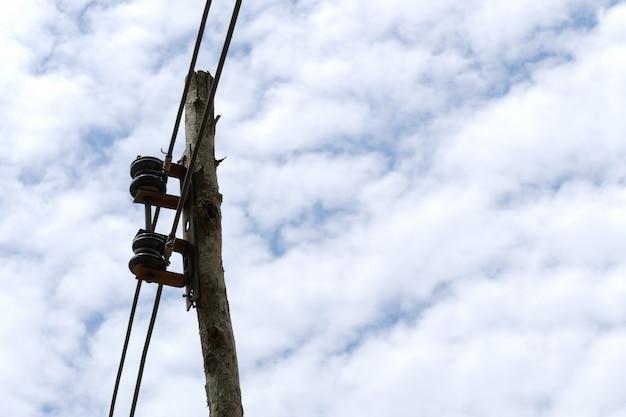 Strompfosten mit hintergrund des blauen himmels und der wolke