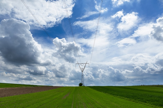 Stromübertragungsmast vor blauem himmel silhouettiert