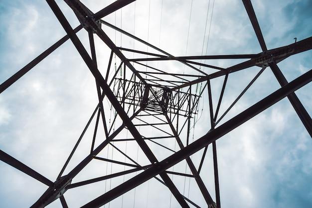Stromverteilungsturm mit kopienraum. hochspannungsleitungen unter bewölktem himmel. unbedeutende ansicht von unterhalb über pfosten mit drähten bei bewölktem wetter. atmosphärischer elektrischer hintergrund.