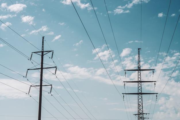 Stromverteilungsturm mit kopienraum. hochspannungsleitungen unter bewölktem himmel. unbedeutende ansicht von unterhalb über pfosten mit drähten bei bewölktem wetter.