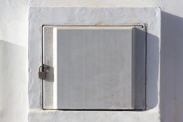 Stromzählerbox mit vorhängeschloss an weißer wand verschlossen
