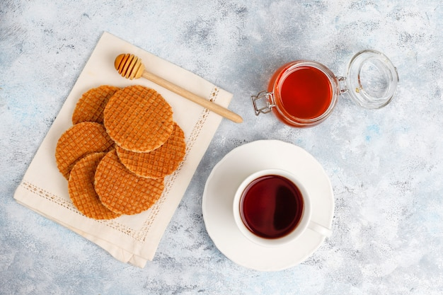 Stroopwafels, karamell-holländische waffeln mit tee oder kaffee und honig auf beton