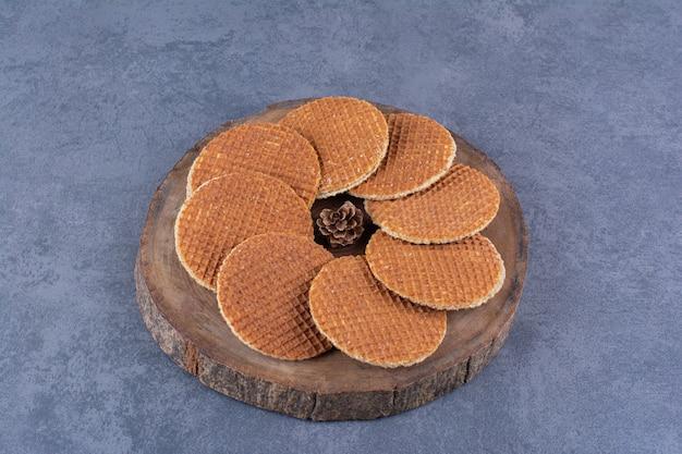 Stroopwafels mit tannenzapfen isoliert in einer holzplatte auf einem stein. hochwertiges foto