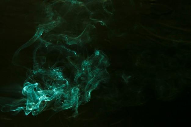 Strudel des grünen rauches auf dunklem hintergrund