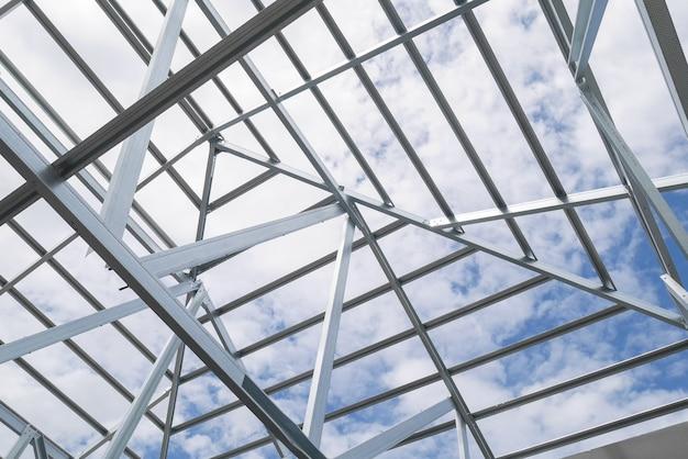 Struktur des stahldachrahmens mit blauem himmel und wolken an der baustelle