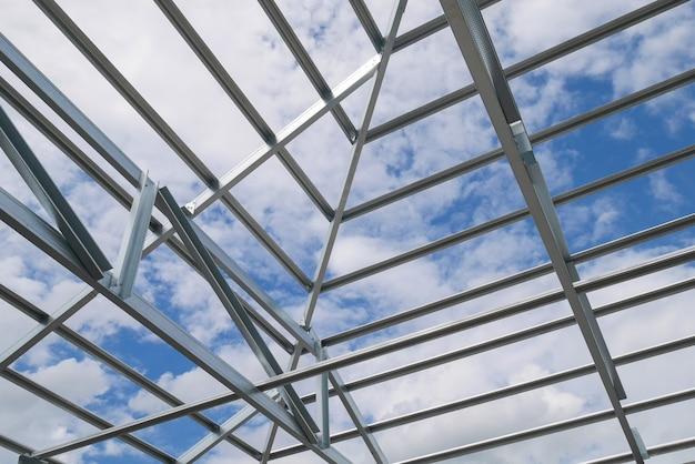 Struktur des stahldachrahmens mit blauem himmel und wolken