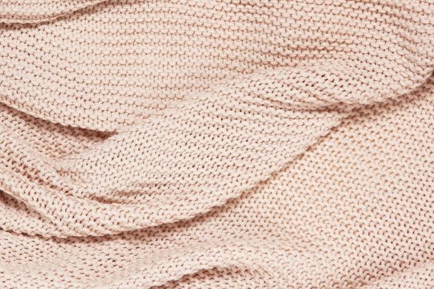 Strukturierte oberfläche aus gestricktem baumwollwellenplaid, draufsicht, nahaufnahme. weicher staubiger rosa pastellwollhintergrund.