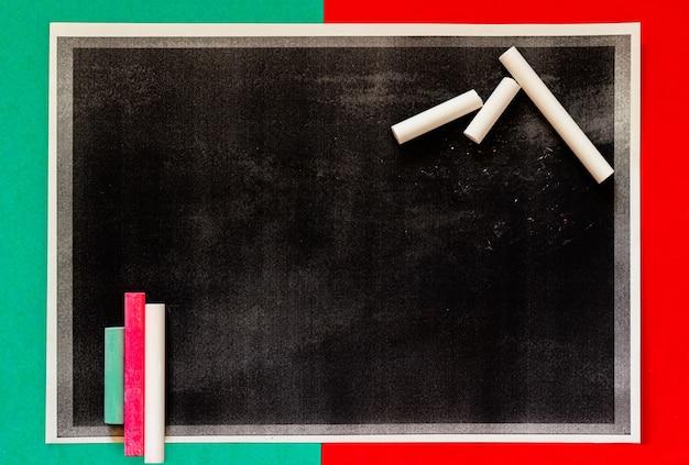 Strukturierte schwarze tafel mit farbigen und weißen kreiden für den unterricht in der college-klasse.