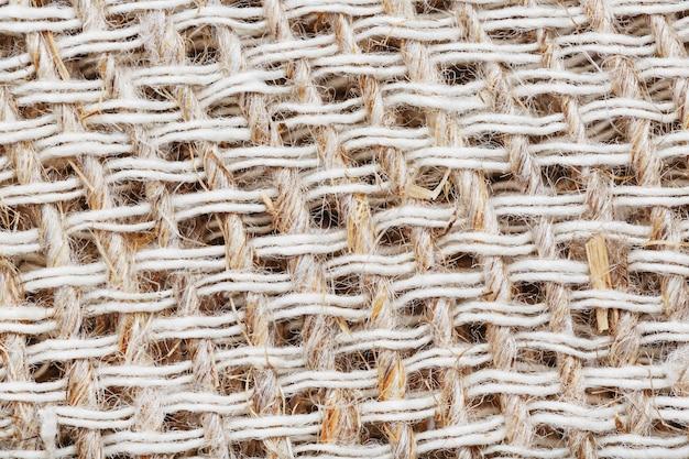 Strukturierter hintergrund aus stoff aus sackleinenfasern mit fasern im vollbildmodus. makro