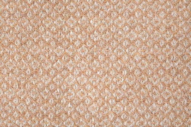 Strukturierter hintergrund des braunen und weißen geometrischen wollgewebes, maschinengewebte musterstruktur. leichte bettdecke oder überwurf-nahaufnahme
