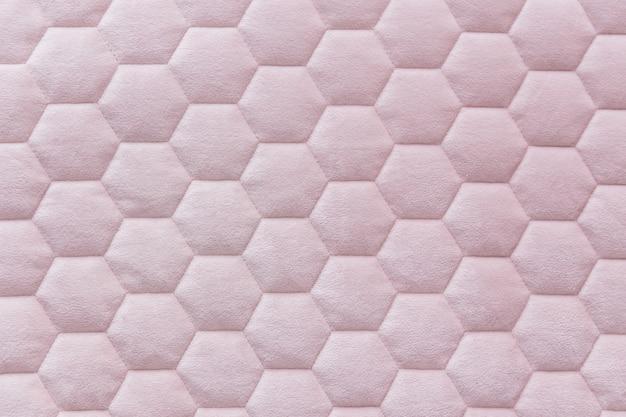 Strukturierter hintergrund des rosa sechseckgittergewebes.