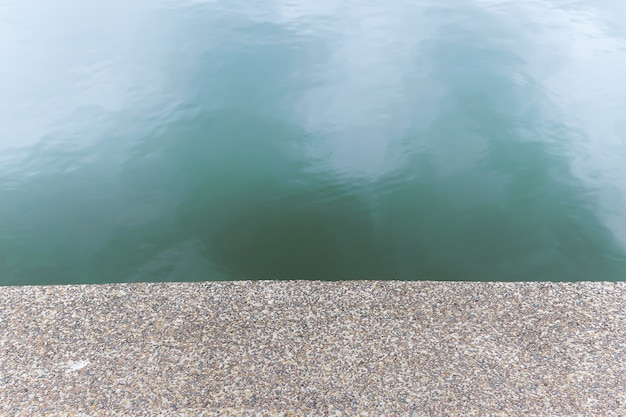 Strukturierter kieselsteinboden neben dem fluss. die musterbodenshow als nahtloser hintergrund.