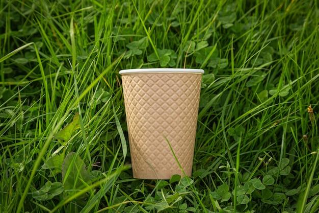 Strukturierter pappbecher liegt im üppigen gras