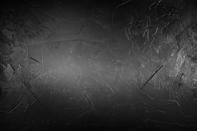 Strukturierter schwarzer beton mit hellen bereichen im hintergrund