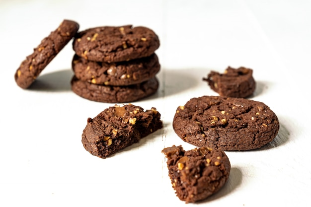Stuck von hausgemachten amerikanischen schokoladenplätzchen mit nüssen auf weißem hölzernem hintergrund. frisches gebäck.