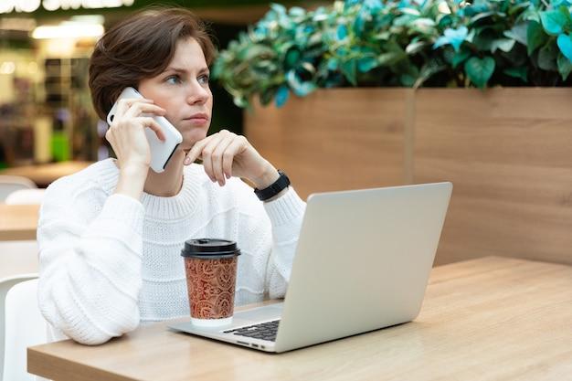 Student arbeitet an einem laptop in einem café in einem einkaufszentrum, freiberuflich und fernarbeitskonzept. spricht am telefon, freut sich nachdenklich.