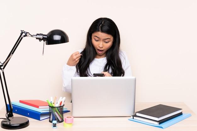 Student asiatisches mädchen in einem arbeitsplatz mit einem laptop auf beige wand überrascht und eine nachricht senden