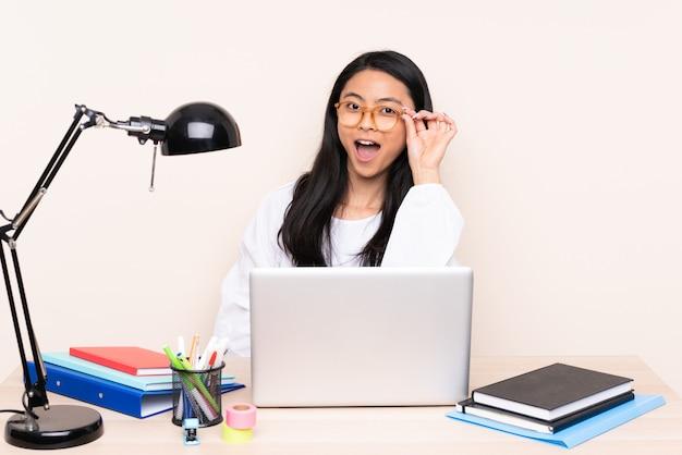 Student asiatisches mädchen in einem arbeitsplatz mit einem laptop lokalisiert auf beige wand mit brille und überrascht