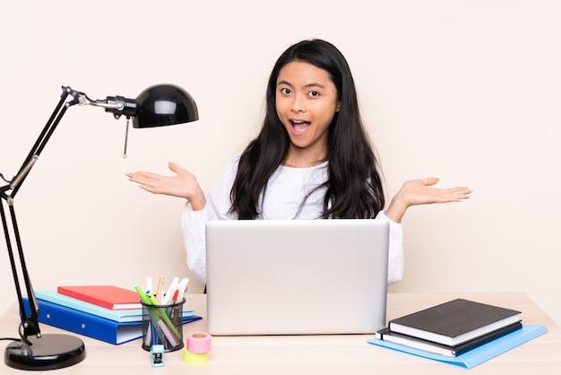 Student asiatisches mädchen in einem arbeitsplatz mit einem laptop lokalisiert auf beigem hintergrund mit schockiertem gesichtsausdruck