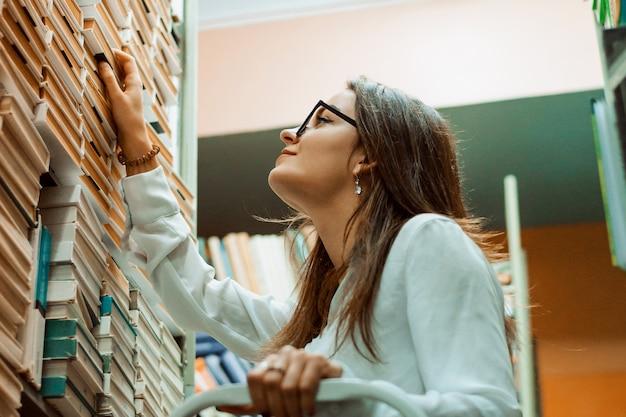Student auf der leiter auf der suche nach einem buch in der öffentlichen bibliothek