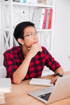 Student, der an ihm laptop im klassenzimmer arbeitet. in der nähe von büchern sitzen und notizen schreiben. sieh zur seite