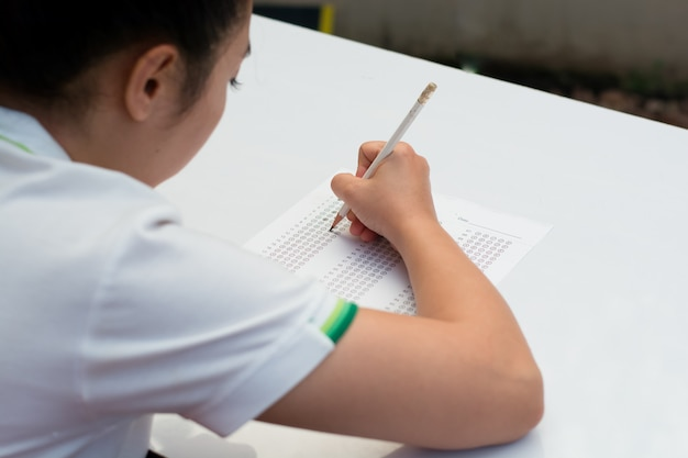 Student, der antworten zu einem test mit einem bleistift ausfüllt.