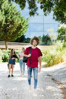 Student, der auf dem campus mit rucksack geht