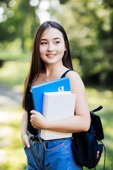 Student, der bücher hält, die auf dem campus gehen, lächelnd zur klasse gehen. junge lächelnde gemischtrassige asiatische frau mädchen mit tasche im freien porträt.