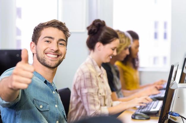 Student, der daumen oben in computerklasse gestikuliert