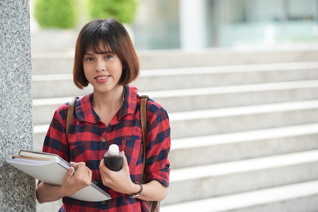 Student, der die lehrbücher stehen an der collegetreppe betrachtet kamera hält