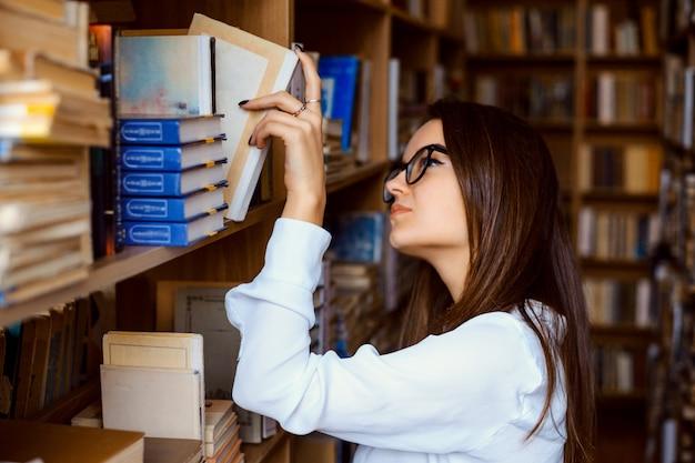 Student, der ein buch aus einem regal in der bibliothek nimmt