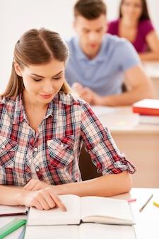 Student, der ein buch liest. draufsicht einer schönen studentin, die ein buch liest, während sie im klassenzimmer sitzt, während andere studenten hinter ihr in einer reihe sitzen?