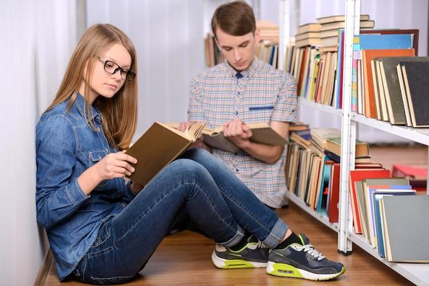 Student, der ein buch liest und einen laptop in der bibliothek verwendet