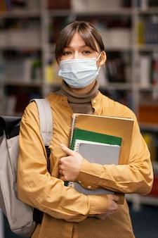 Student, der eine medizinische maske in der bibliothek trägt