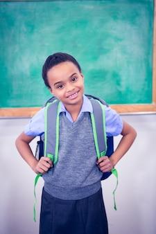 Student, der eine schultasche lächelt und trägt