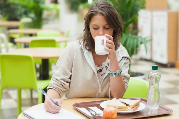 Student, der hausarbeit tut und in der cafeteria frühstückt