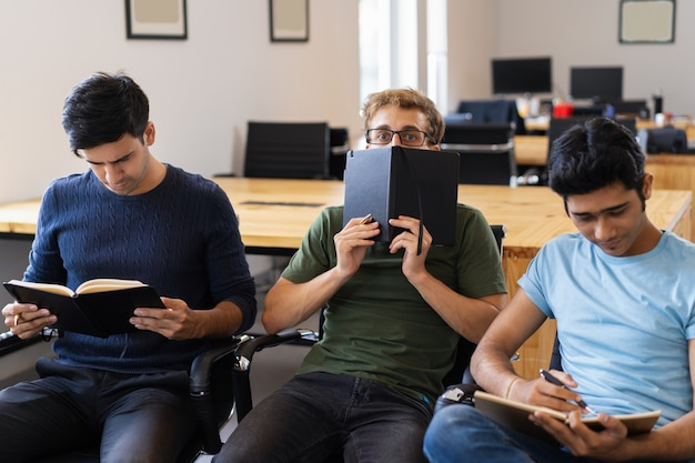 Student, der hinter notizbuch sich versteckt und zwischen zwei freunden sitzt