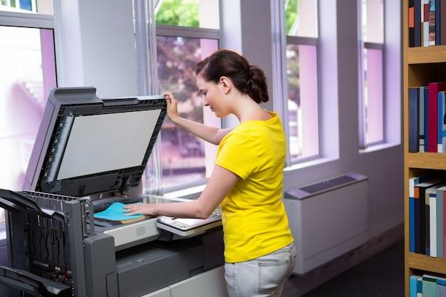 Student, der ihr buch in der bibliothek kopiert
