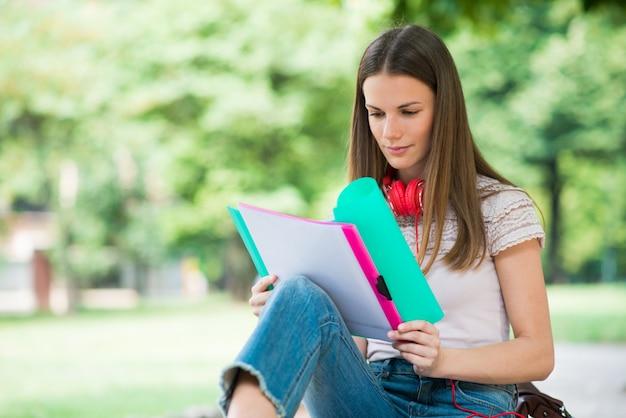 Student, der in einem park vor der schule studiert