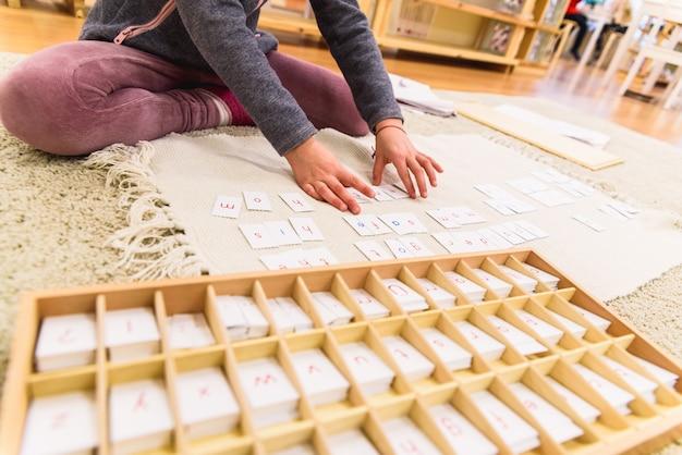 Student, der karten mit buchstaben verwendet, um wörter zu verfassen, sitzend auf dem klassenzimmerboden