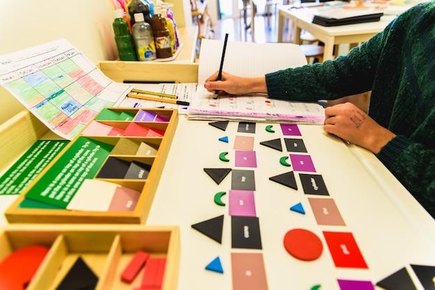 Student, der material verwendet, um geometrische formen in einer montessorischule zu lernen.