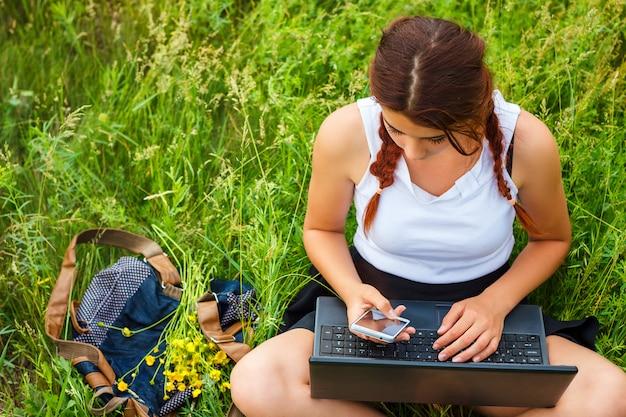 Student, der mit einem laptop auf dem gras, draufsicht sitzt