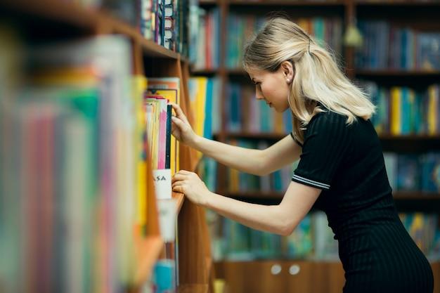 Student, der nach büchern in einer bibliothek sucht