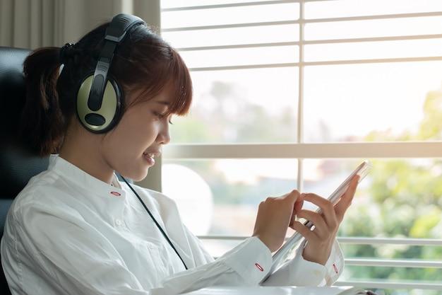 Student, der on-line-studienkonzept lernt: schönes asiatisches mädchen, das mit kopfhörern hört