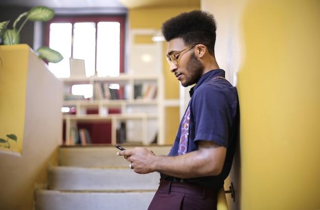 Student, der sein telefon bei der stellung auf der treppe der schule überprüft