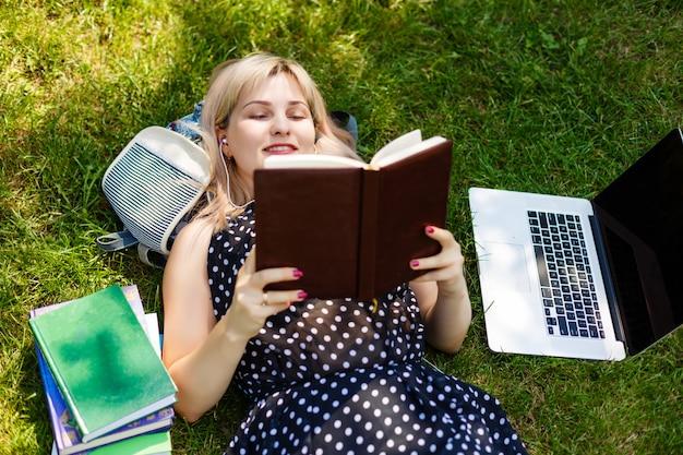 Student, der sich auf dem gras arbeitet an laptop am campus hinlegt