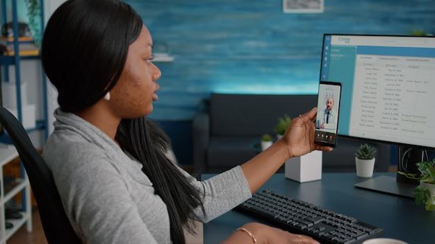 Student, der während der virtuellen telemedizin-konferenz im gesundheitswesen telefon in den händen hält
