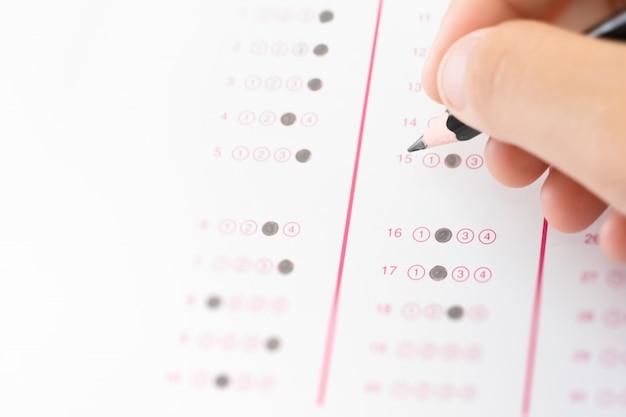 Student des bleistifts an hand zur schriftlichen beantwortung der frage der prüfungsprüfung
