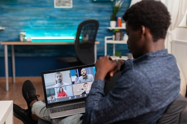 Student diskutiert marketingidee mit college-team während online-videoanruf-telekonferenz-meeting mit e-learning-universitätsplattform. konferenz-telearbeit auf laptop im wohnzimmer. computerbenutzer