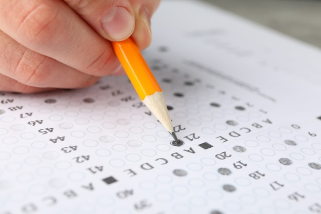 Student füllt antworten testblatt, nahaufnahme Premium Fotos